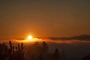 The sun sets behind the Olympics it's last light illuminates a Puget Sound fog bank.