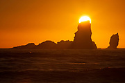 The setting sun seems to be balanced on one of the Sea Lion Rocks, a series of sea stacks off the northern Oregon coast. The rocks were formed by ancient lava flows, which have since been eroded by constant pounding from Pacific Ocean waves. These sea stacks are located near Ecola State Park, north of Cannon Beach, Oregon.