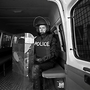 Polizistin mit Helm und Schild im Bus, policiËre avec casque et bouclier anti-manif, policewoman in bus with shield. © Romano P. Riedo