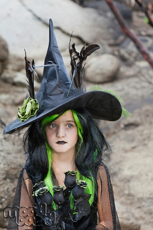 Girl dressed as witch holding black roses