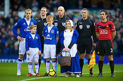 LIVERPOOL, ENGLAND - Saturday, February 20, 2010: Everton's captain Phil Neville and brother, Manchester United's captain Gary Neville line up with mascots and officials before the Premiership match at Goodison Park. (Photo by: David Rawcliffe/Propaganda)