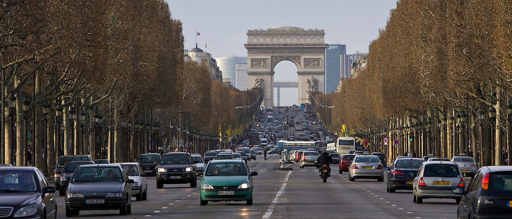 Traffic travelling on Champs-Élysées by Arc de Triomphe, Central Paris, France