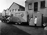 Picture of Loading Tayto Crisps at Tayto, Rathmines.31/01/1958..In 1954 Joe Spud Murphy began what is today's largest snackfood company with just two rented rooms off Moore Street, Dublin. Truly, a remarkable story of one man's determination, his initial set up costs ran to a grand total of £500. The entire staff consisted of Joe, his eight employees and a single van...At the time Tayto crisps sold for 4 pence per bag! They were sold in beautiful tin boxes that contained 18 bags of crisps and sold to shops for 4 shillings. The crisps bags were hand-glued with a tiny paintbrush to guarantee that trademark Tayto freshness..Not many people realise that it was Joe Spud Murphy who actually invented the now world renowned Cheese & Onion flavour- with a little input from Mr. Tayto, of course..Pioneering as always, Joe Murphy placed ads in the local newspapers which promoted the full list in the original Tayto range: Plain Golden, Onion, Cheese & Onion and Cheese flavoured crisps..In 1954, Tayto sold 347 packs per day. Today, Tayto sells over 525 packs a minute!.