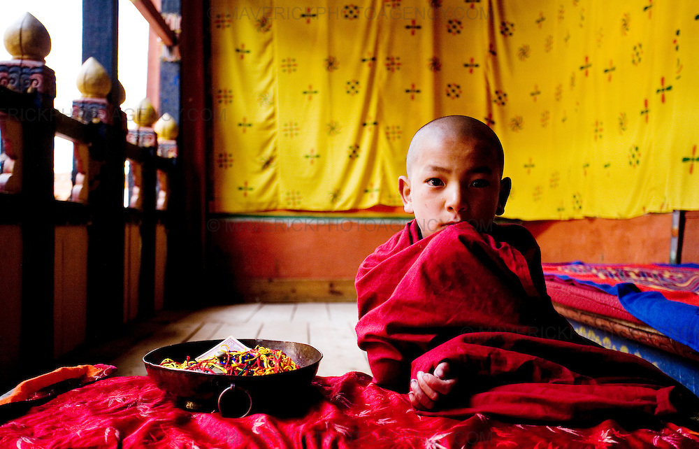 A  young monk sits in a room at Rinpung Dzong, Paro.  Commonly described as the last Himalayan Shangrila, Bhutan is a country of unique serenity, harmony, and beauty. Nestled between India, China, and Tibet, this independent country whose name translates as 'the Land of the Thunder Dragon' has for the past 300 years  proactively followed a policy of isolation and cultural protection. Travel in and out of the country is strictly regulated, and the impact of outside influences on the local culture is carefully monitored. Spirituality is an important aspect of Bhutanese culture, with Buddhism being interlinked with everyday life. Gross National Happiness (GNH), as opposed to GNP/GDP, forms the cornerstone of its development strategy which focuses on a holistic development strategy that complements its cultural and Buddhist spiritual values.
