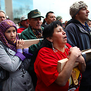 Sue Teton Pound, a Nooksack Indian, right, and Fareeda Khojandi of Afghanistan help carry a totem pole estimated to weigh nearly 5,000 pounds during a procession to the Seattle Center from pier 57 on Sunday February 26, 2012 in Seattle. The 33-foot tall totem pole was erected Sunday in honor of slain Native American woodcarver John T. Williams. Williams was shot and killed by a Seattle Police officer in 2010. The shooting was later ruled unjustified.  (Joshua Trujillo, seattlepi.com)