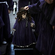 A child penitent touches a figure representing a baby Jesus the Nazarene as they parade during the Maundy Thursday procession on April 17, 2014 in the northern Spanish Basque village of Segura. PHOTO/ RAFA RIVAS