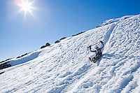 A happy man glisading down a little chute on Mount Rainier's Muir snow field.