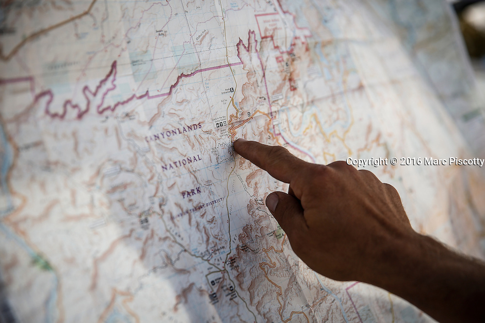 SHOT 10/14/16 12:33:00 PM - Pointing out the route along the White Rim trail, a mountain biking trip in Canyonlands National Park just outside of Moab, Utah. The White Rim Road is a 71.2-mile-long unpaved four-wheel drive road that traverses the top of the White Rim Sandstone formation below the Island in the Sky mesa of Canyonlands National Park in southern Utah in the United States. The road was constructed in the 1950s by the Atomic Energy Commission to provide access for individual prospectors intent on mining uranium deposits for use in nuclear weapons production during the Cold War. Four-wheel drive vehicles and mountain bikes are the most common modes of transport though horseback riding and hiking are also permitted.<br /> (Photo by Marc Piscotty / &copy; 2016)
