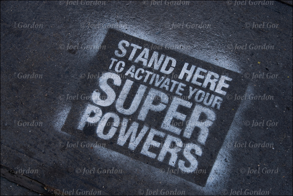 Stencil Art painted with white paint on sidewalk &quot;Stand Here to Activate Your Super Powers&quot;.<br /> <br /> Bel Linquist is the artist and this is his street art project and his tag is #bellinquist #superpowersactivated.