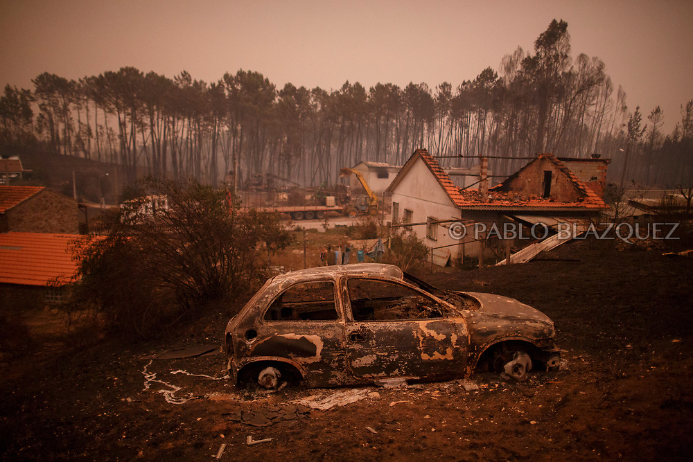 LEIRIA, PORTUGAL - JUNE 18:  A burned car stand next to burned houses after a wildfire took dozens of lives on June 18, 2017 near Castanheira de Pera, in Leiria district, Portugal. On Saturday night, a forest fire became uncontrollable in the Leiria district, killing at least 62 people and leaving many injured. Some of the victims died inside their cars as they tried to flee the area.  (Photo by Pablo Blazquez Dominguez/Getty Images)