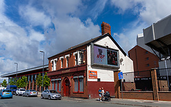 """LIVERPOOL, ENGLAND - Monday, August 3, 2020: A Nike advert """"Tell Us Never"""" is shown on a hording on The Albert pub oustide Liverpool's Spion Kop at Anfield. Liverpool's new kit supplier Nike replaces New Balance in a five year deal reported to be worth $39.5 per year. (Pic by David Rawcliffe/Propaganda)"""