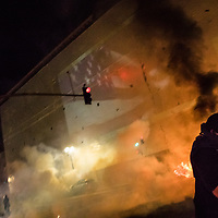 NOVEMBER 9, 2016 - OAKLAND, CA: An Anti-Trump protester runs from tear gas fired by Police to disperse a crowd that had gathered after protesters dismantled construction barricades at the new Uber headquarters, to use as fodder for a fire, in Oakland, California on November 9, 2016. (Photo by Philip Pacheco)