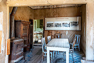 Inside the Tom Miller house at Bodie; view of dining room with stove and table, kitchen visible through doorway.