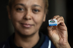 """© Licensed to London News Pictures . 22/04/2020. Manchester, UK. In an echo of Health Secretary Matt Hancock's pose with a """"CARE"""" badge , Cleaner SIMONE MATTIS (43) , holds a commemorative badge , being given as a gift to those who have worked at the NHS Nightingale Hospital in Manchester . The National Health Service has built a 648 bed field hospital for the treatment of Covid-19 patients , at the historical railway station terminus which now forms the main hall of the Manchester Central Convention Centre . The facility is treating patients from across the North West of England , providing them with general medical care and oxygen therapy after discharge from Intensive Care Units . Photo credit : Joel Goodman/LNP"""