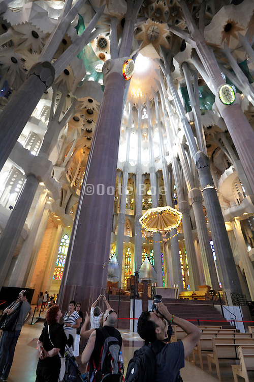 tourists looking and photographing the ceiling Sagrada Familia Barcelona Spain