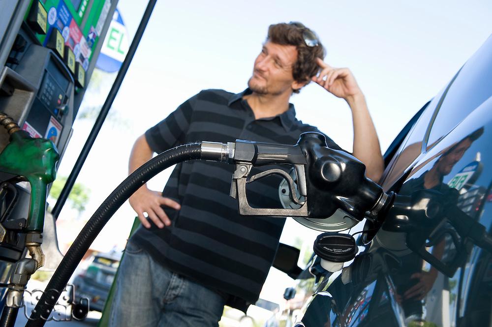 Smiling man refueling car at natural gas station