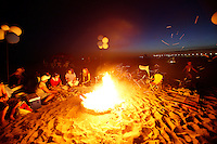 21 June 2008:  Friends gather around wood burning beach bonfire at tower 9 in Huntington Beach, California at sunset.