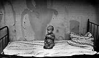Child poverty. Single baby sitting alone. St Petersburg, Russia 1994