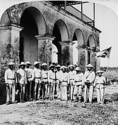 Officers of Gen. Gomez' Army, Remedios, Cuba.  Twelve men standing in front of a building, they are holding weapons; one man is holding a flag. stereograph. c1899. During the Spanish American War