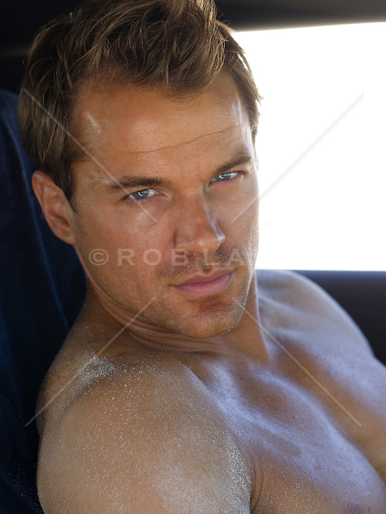 man with blue eyes, no shirt and a tan looking at camera