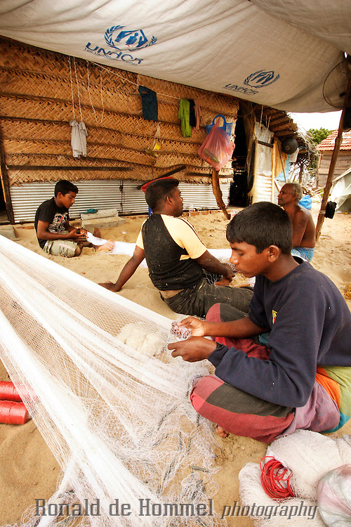 Fishermen, tsunami victims, in Batticaloa are fixing their nets in front of a temporary shelter, provided by international donors.