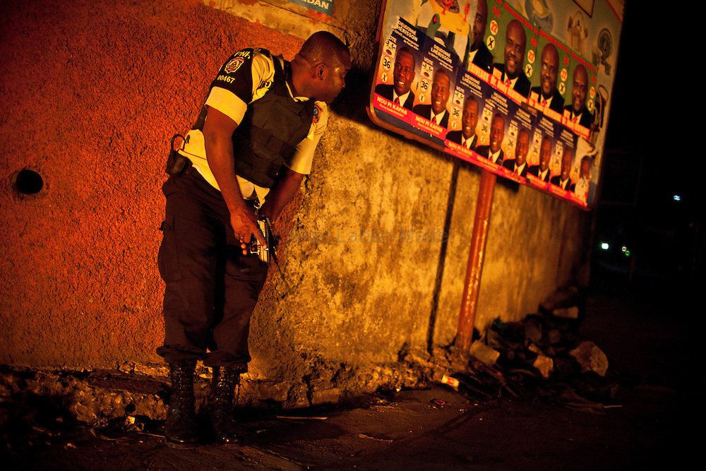 A policeman protects himself as Martelly's supporters demonstrate, in the streets of Port-au-Prince, to protest against the results of the presidential elections and the defeat of their leader, Michel Martelly.