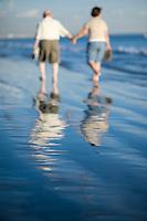 Senior couple walking on beach, reflecting in water