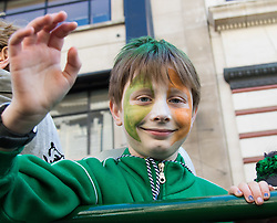 London, March 13th 2016. The annual St Patrick's Day Parade takes place in the Capital with various groups from the Irish community as well as contingents from other ethnicities taking part in a procession from Green Park to Trafalgar Square.  PICTURED: His face painted in Irish colours, a boy waves from one of the floats. &copy;Paul Davey<br /> FOR LICENCING CONTACT: Paul Davey +44 (0) 7966 016 296 paul@pauldaveycreative.co.uk