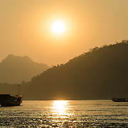 Boats at sunset on the Mekong River near Luang Prabang, Laos.