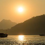 Boats at sunset on the Mekong River near Luang Prabang, Laos.