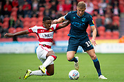 Alfie Kilgour of Bristol Rovers is tackled by Donervon Daniels Of Doncaster Rovers during the EFL Sky Bet League 1 match between Doncaster Rovers and Bristol Rovers at the Keepmoat Stadium, Doncaster, England on 19 October 2019.
