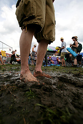 30 April 2006. New Orleans, Louisiana. Jazzfest . <br /> The first New Orleans Jazz and Heritage festival following the disaster of Hurricane Katrina. A fan squelches his feet in the mud after the rains at the Acura stage.<br /> Photo ©Charlie Varley/varleypix.com<br /> All rights reserved.