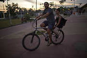 Gilmar Bezerra da Costa drives her daughter, Sabrina Lais, back home after a ballet class outside the Biblioteca Parque in Manguinhos neighbourhood in Rio de Janeiro, Brazil, Monday, June 11, 2018.  The Manguinhos community ballet has been a reprieve from the violence and poverty that afflicts its namesake neighborhood for hundreds of girls who have benefitted from free dance classes since 2012. (Dado Galdieri for The New York Times)