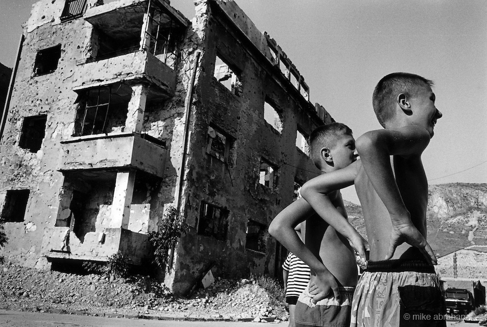 """Boys playing basketball in the ruins on the front line between Muslim East Mostar and Croat West Mostar. It was destroyed by systemic bombardment from Croat guns during the Croat Muslim War, when the Croats endeavored to """" cleanse"""" the town of non Croats."""