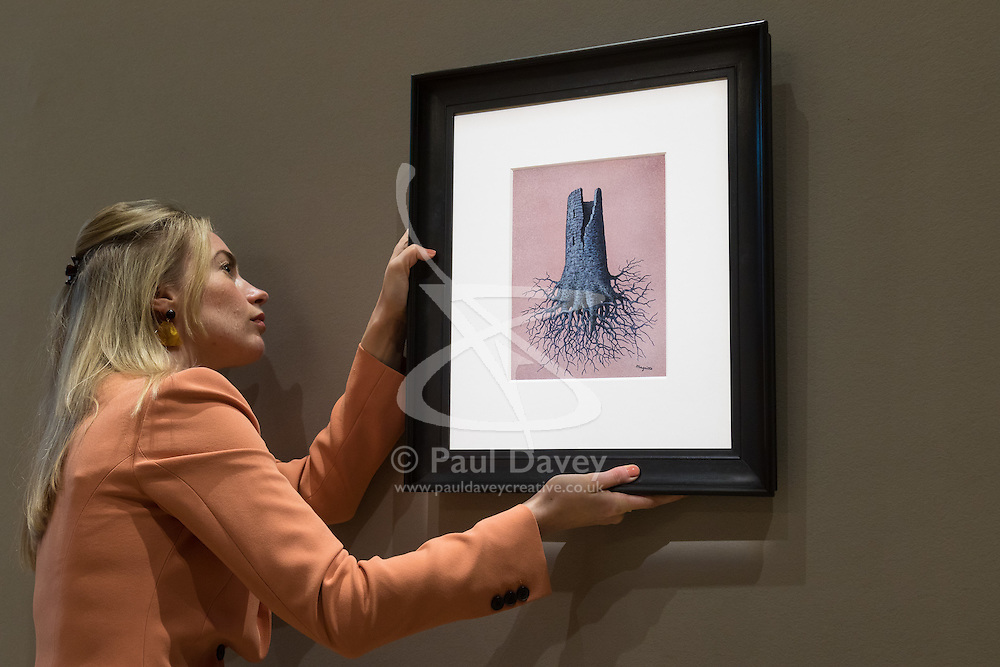 Bonhams, London, February 27th 2017. A member of Bonhams staff hangs René Magritte's 'La folie Alamyer', valued between £300,000 and £500,000, at the Bonhams impressionist and modern art sale press preview at their Mayfair gallery in London.