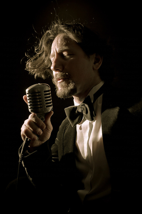 A man wearing a bow tie singing into a microphone