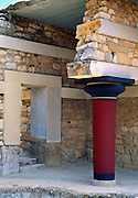 A red Minoan pillar is restored at Knossos palace, in Heraklion (Iraklion), Crete, Greece, Europe. Knossos is a Minoan archeological site associated with the Labyrinth and Minotaur of Greek mythology. The Bronze Age palace of Knossos was first built around 1900 BC, destroyed by a large earthquake or foreign invaders in 1700 BC, rebuilt more grandly, then damaged several more times by earthquakes, by invasions, and in 1450 BC by the colossal volcanic eruption of Thera (modern Thira or Santorini). Invading Mycenaeans used Knossos as their capital as they ruled the island of Crete until 1375 BC. Archaeologist Arthur Evans excavated the Palace at Knossos from 1900-1905 and named the Minoan civilization of Crete after king Minos from Greek mythology. Homer's epic poems of the Iliad and Odyssey are the first Greek literature to mention Minos as a king of Knossos, Crete. Minos was son of Zeus and Europa. Every nine years Minos made King Aegeus pick seven men and seven women to go to the Labyrinth to be eaten by the Minotaur, a creature half man and half bull. After his death, legendary Minos became a judge of the dead in Hades. The vast building complex at Knossos is popularly thought to be the site of the Labyrinth, which Greek mythology says was designed by architect Daedalus with such complexity that no one could ever find its exit.