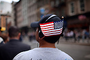 A boy holding a US flag on his hat is walking on the street and listening to music in Lower Manhattan, New York, USA, on the 10th anniversary of the 9/11 attacks on the Word Trade Centre.