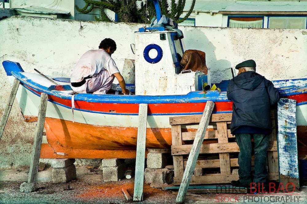 Men working on a boat.<br /> Oia village. Santorini island, Greece, Europe
