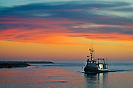The 87' Graham Hull Marine Survey Vessel entering the harbor at sunset, Morro Bay, California
