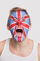 Portrait of young Caucasian man with British flag painted on face cheering against white background