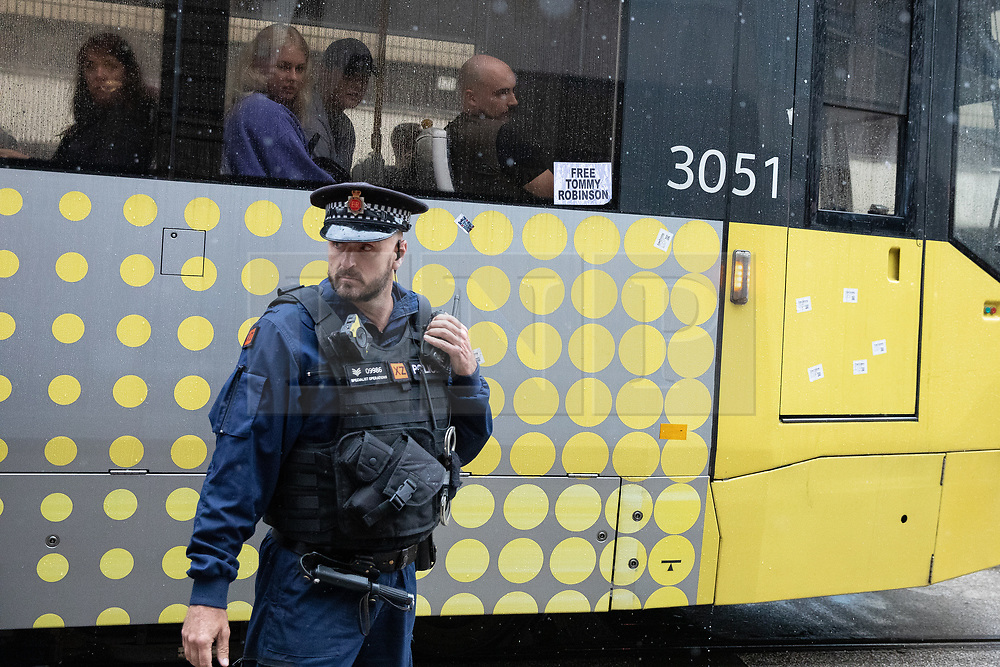 © Licensed to London News Pictures . 27/07/2019. Manchester, UK.  Police intervene after demonstrators temporarily blocks tram lines in and out of the city . An unannounced demonstration in support of jailed former EDL leader Stephen Yaxley-Lennon (aka Tommy Robinson ) in Manchester City centre . Up to 200 supporters chanted in support of Yaxley-Lennon as they marched past shoppers . Photo credit: Joel Goodman/LNP