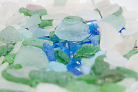 A plate full of beach glass shows the variety of blues, greens and whites of ocean-tumbled glass.