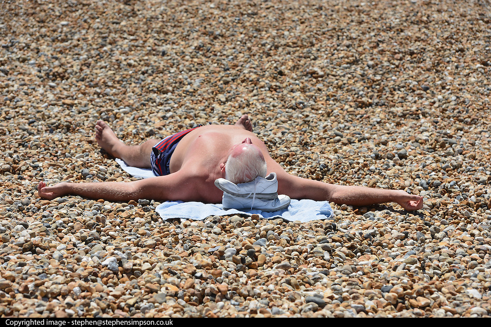 © Licensed to London News Pictures. 03/07/2014. Bognor Regis, UK. A man sunbathes.  People enjoy the hot sunny weather at the seaside resort of Bognor Regis today 3rd July 2014. Forecasters are predicting it to be the hottest day of 2014 so far. Photo credit : Stephen Simpson/LNP