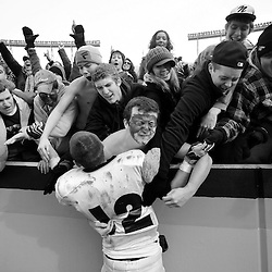 047-State Championship<br /> Northside High School football player, Tyler Fisher (middle, #12), is swarmed by fans at the end of the game against Bruton High School at the conclusion of the Region III State High School Football Championship game Saturday in Blacksburg. Northside defeated Bruton 20-17 to win the first football state championship in school history.