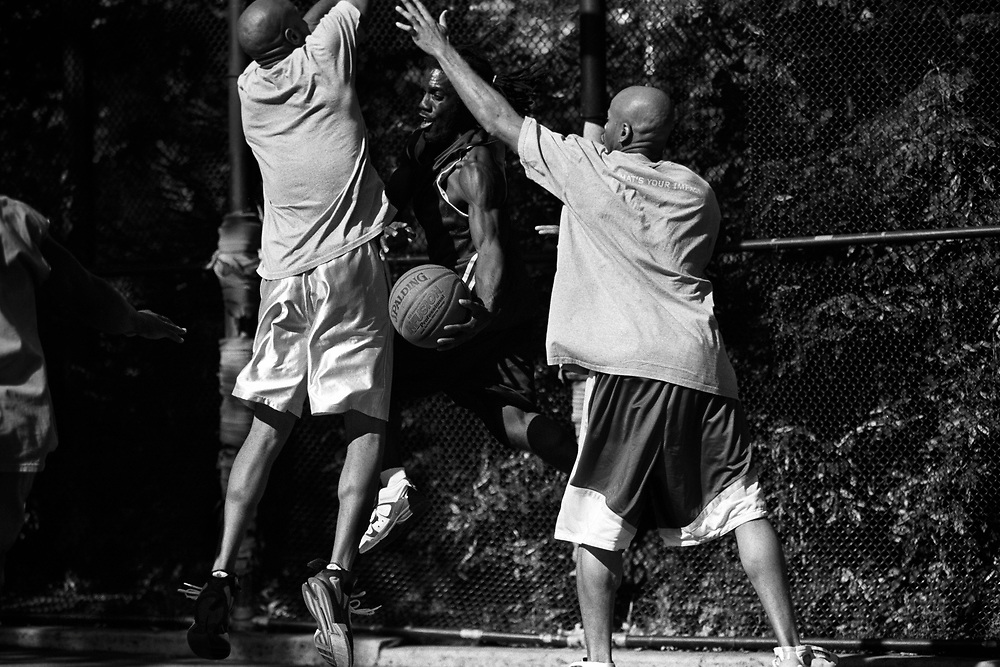 October 2nd 2005. New York, New York. United States..Located in the heart of Greenwich Village, the West 4th Street basketball Court, known as ?The Cage?, offers no seating but attracts the best players and a lot of spectators as soon as spring is around the corner..Half the size of a regular basketball court, it creates a fast, high level of play. The more people watch, the more intense the games get. « The Cage » is a free show. Amazing actions, insults and fights sometimes, create tensions among and inside the teams. The strongest impose their rules. Charisma is present..?The Cage? is a microcosm. It?s a meeting point for the African American street culture of New York. Often originally from Jamaica or other islands of the Caribbean, they hang out, talk, joke, laugh, comment the game, smoke? Whether they play or not, they?re here, inside ?The Cage?. Everybody knows everybody, they all greet each other, they shake hands and hug: ?Yo, whasup man??.