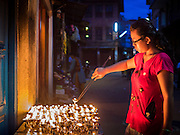 31 JULY 2015 - KATHMANDU, NEPAL: A woman lights butter lamps on a side street in Bouda during the full moon processions around Bodhnath Stupa. Bodhnath Stupa in the Bouda section of Kathmandu is one of the most revered and oldest Buddhist stupas in Nepal. The area has emerged as the center of the Tibetan refugee community in Kathmandu. On full moon nights thousands of Nepali and Tibetan Buddhists come to the stupa and participate in processions around the stupa. The stupa was heavily damaged in the earthquake of 25 April 2015 and people are no longer allowed to climb on the stupa, now they walk around the base and pray with butter lamps.   PHOTO BY JACK KURTZ