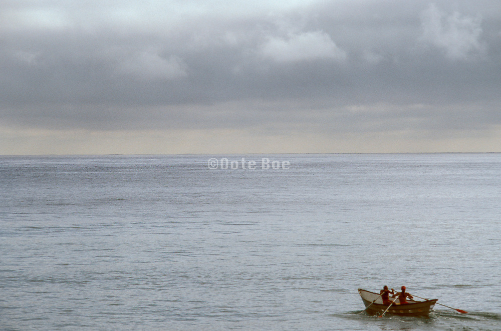 two figures rowing boat amidst vast ocean