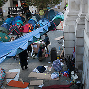 Camping activists slowly waking up under a giant tarpaulin beside the main entrance to the cathedral. Day three of the occupation - and the first Monday.  The Occupy London Stock Exchange movement was formed in London in solidarity with the US based Occupy Wall Street. The movements are a respons and in anger to what is seen by many as corporate greed and a failed banking system being bailed out by the public, - which in return are suffering austerity measures to make up for the billions of lost money. The movement occupied the St Paul's Square in the City of London Sat Oct 15 after it failed to secure and occupy Pator Noster Square and the Stock Exchnage itself.