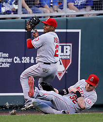 Los Angeles Angels left fielder Josh Hamilton (32) slides into Erick Aybar (2) as the shortstop catches a fly ball hit by Kansas City Royals' Alex Gordon in the third inning of a baseball game at Kauffman Stadium in Kansas City, Mo., Friday, June 27, 2014.  (AP Photo/Colin E. Braley)